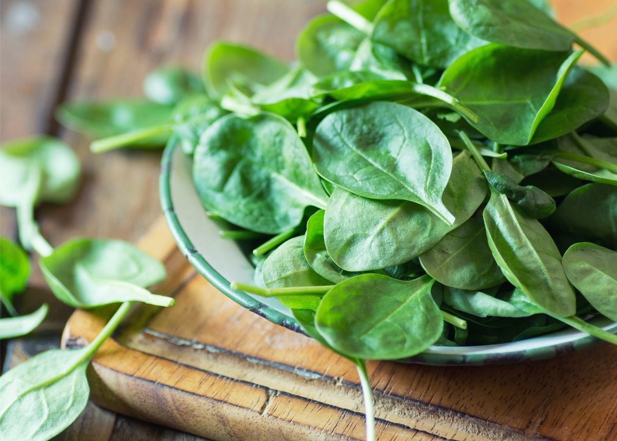 Spinach leaves piled in a shallow bowl on top of a rustic wooden table.
