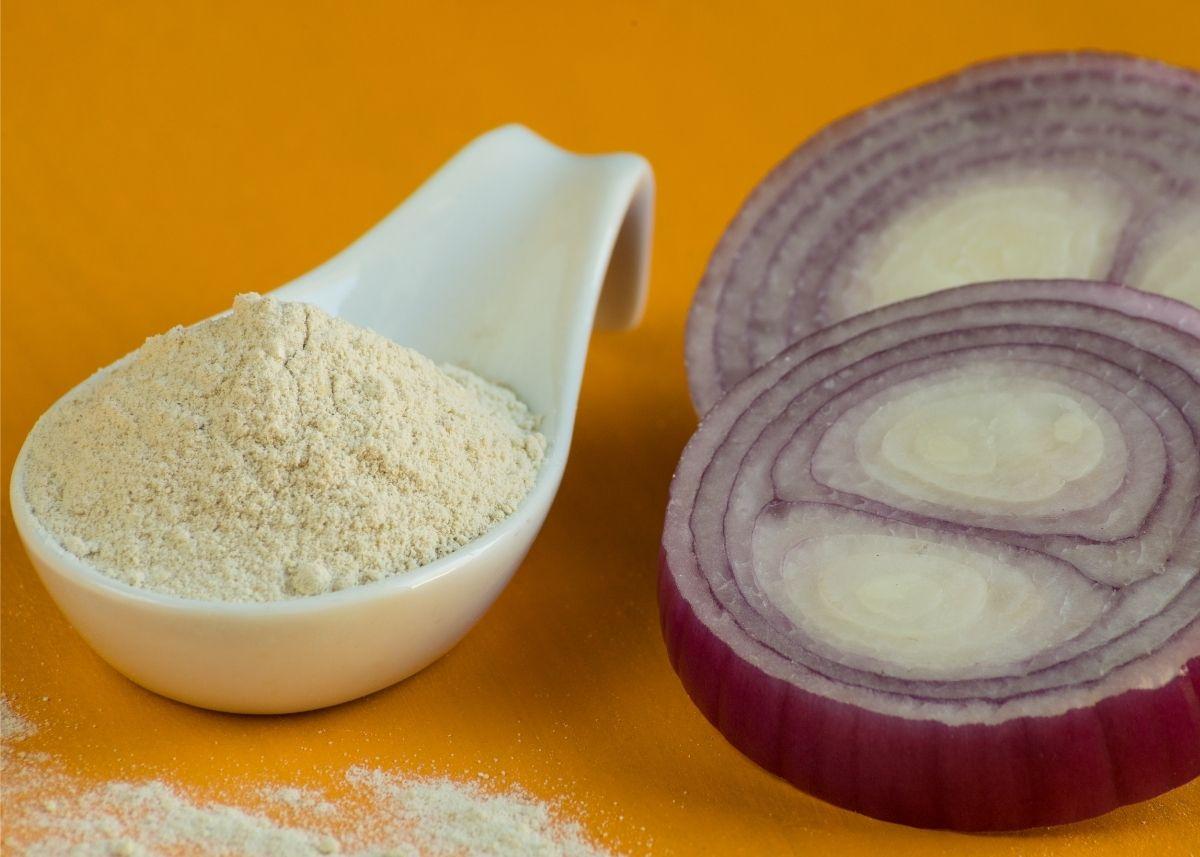 Heaping mound of onion powder on large white spoon next to cut purple onion.