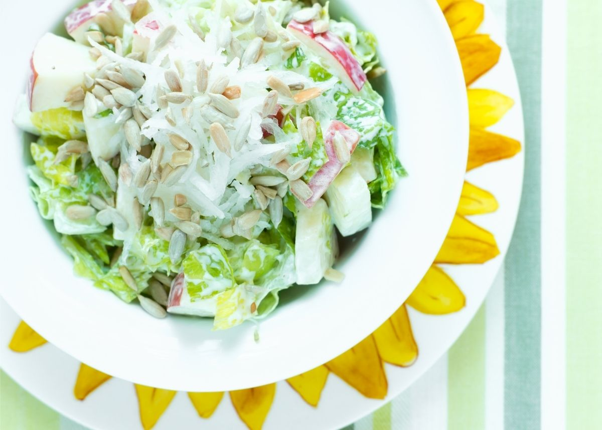 Sunflower seeds garnish a green salad with apples and creamy white dressing.