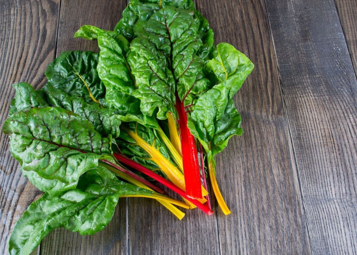 Pile of Swiss chard with yellow and red stems sitting on a rustic wooden table.