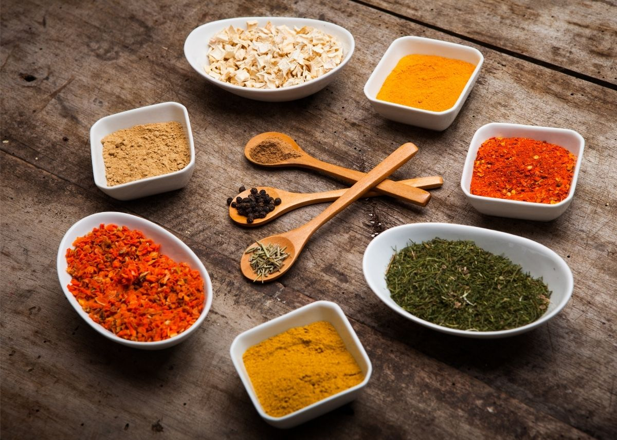 Several different types of exotic spices sit inside various bowls and spoons.