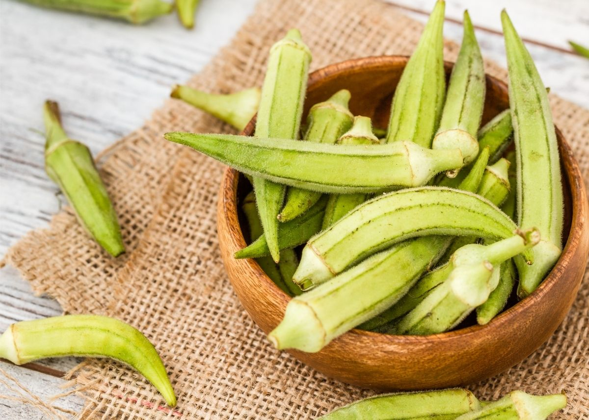 Lots of okra in a wooden bowl sitting on a burlap sack.