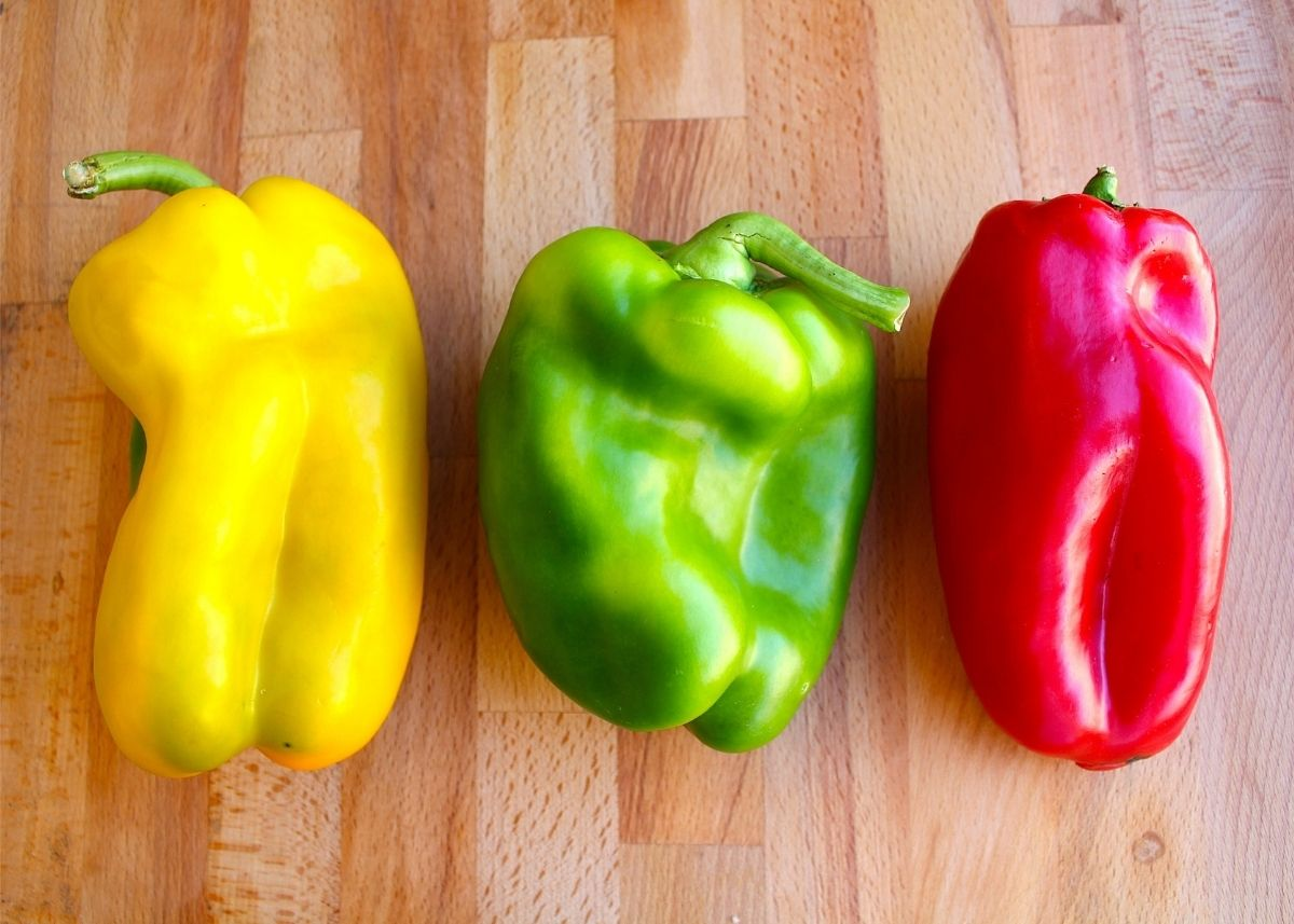 Trio of red, green and yellow bell peppers lined up on a wooden cutting board.
