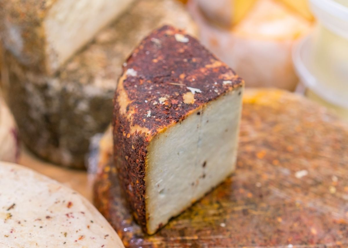 Half of an Anjeo cheese wedge with reddish brown spice coating on top of cheese pile.