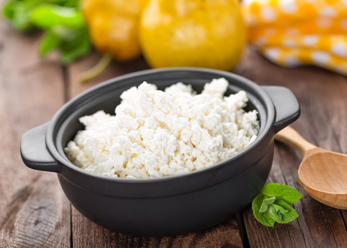 Cottage cheese in a cast iron crock surrounded by yellow and green vegetables.