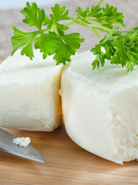 Two large wedges of cotija cheese with green garnish next to a knife.