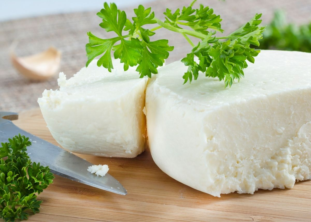 Two large wedges of cotija cheese with green garnish next to a knife on wood cutting board.