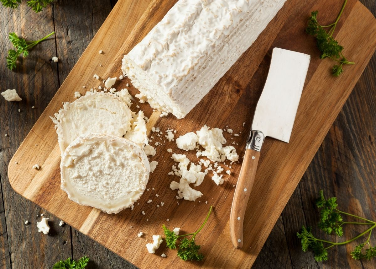 Sliced goat cheese log and goat cheese crumbles on a wooden cutting board next to small cleaver.