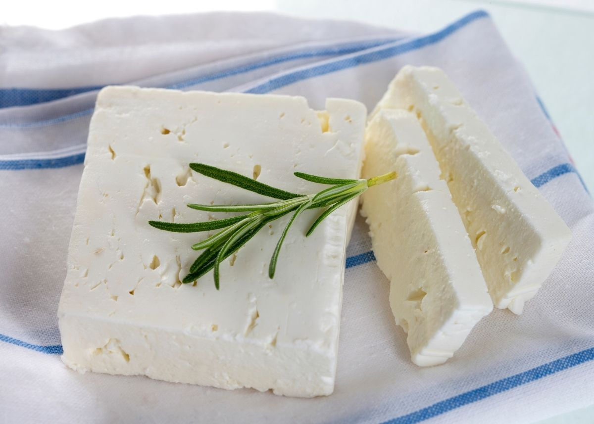Two large slices of feta cheese garnished with rosemary sprig on blue and white striped kitchen towel.