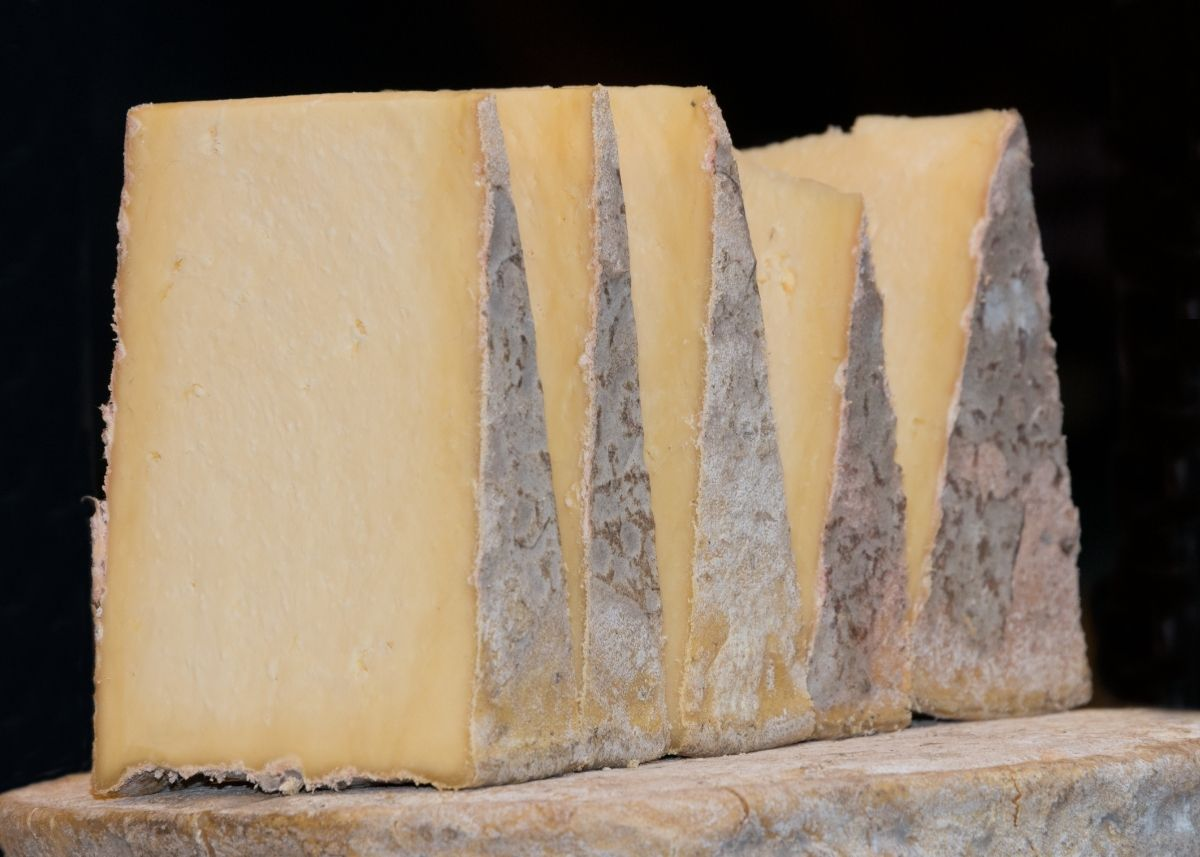 Several triangular Gorwydd Caerphilly cheese wedges standing on a rustic wooden shelf.