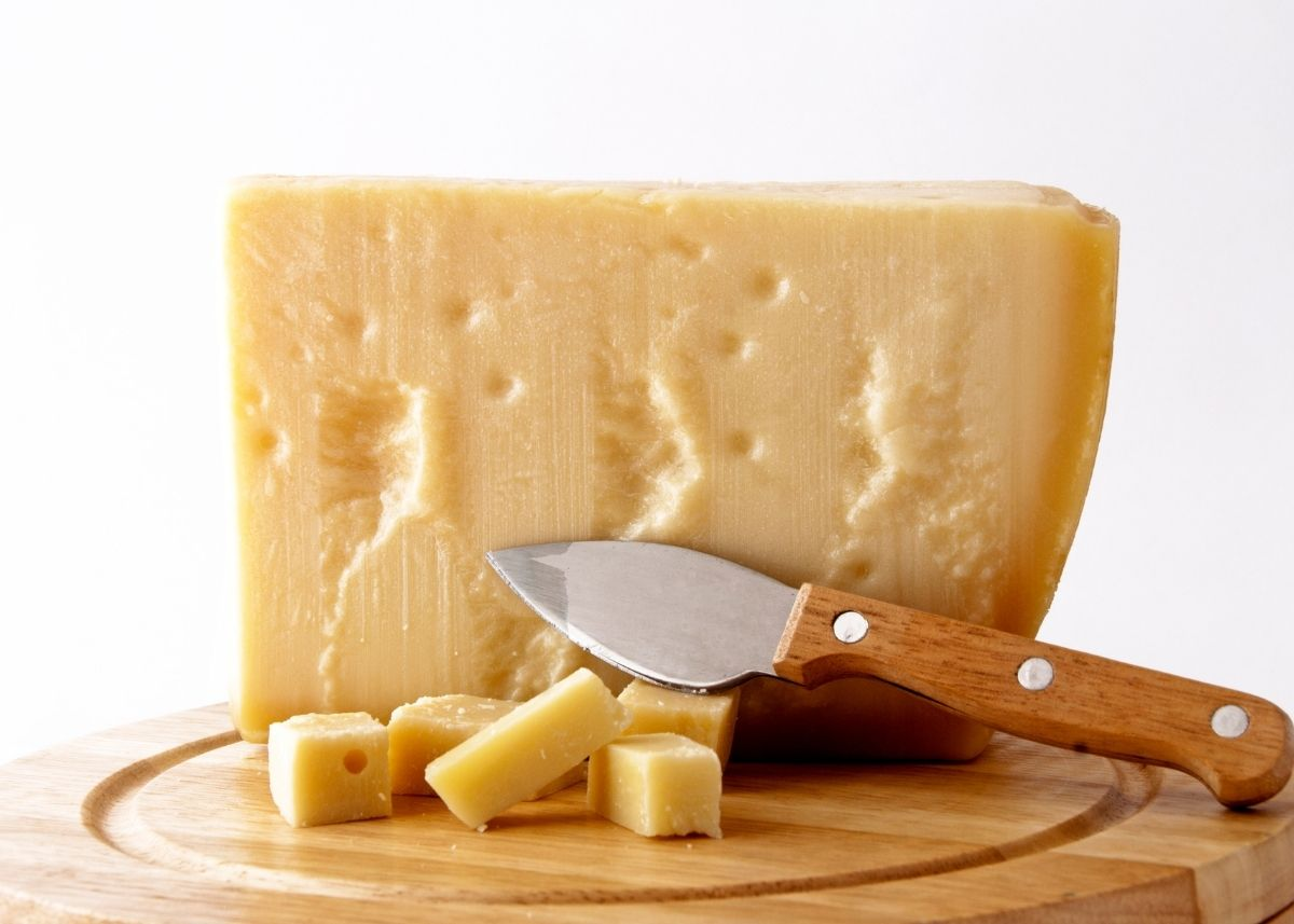 Large portion of a Grana Padano cheese wheel next to slices and cheese knife on a cutting board.