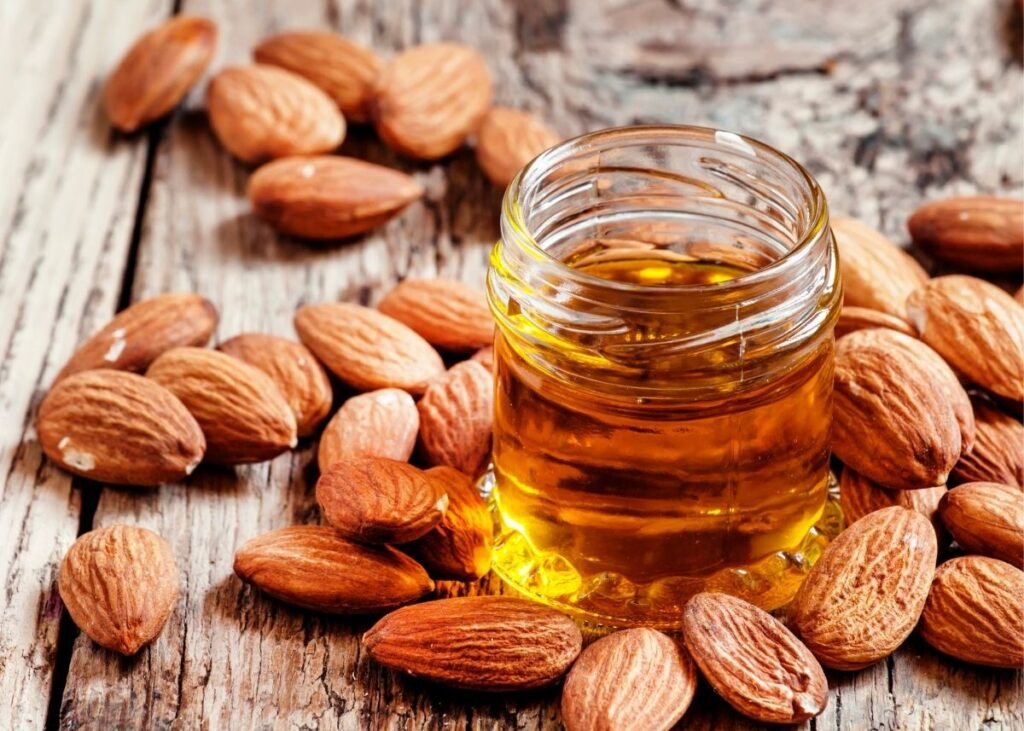 Clear glass jar of almond extract surrounded by almonds on a wooden table.