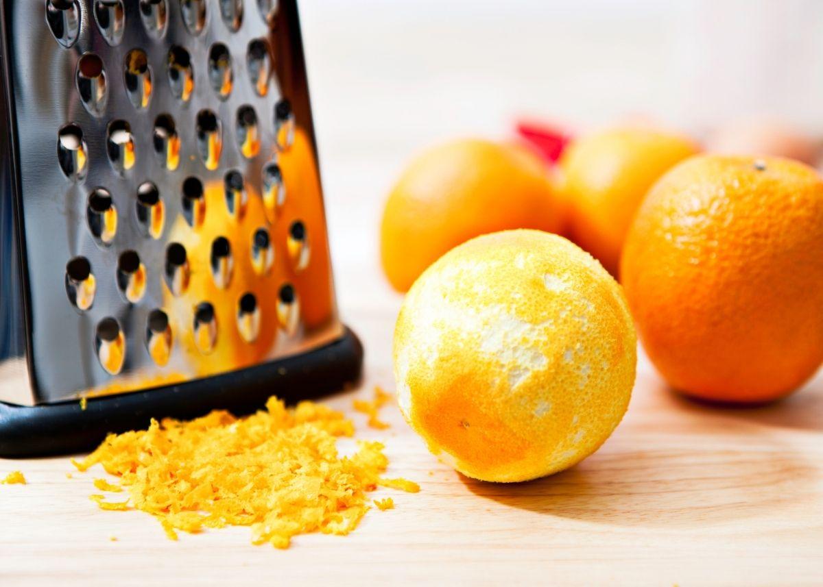 Kitchen grater next to pile of orange zest, a zested orange and several fresh oranges.