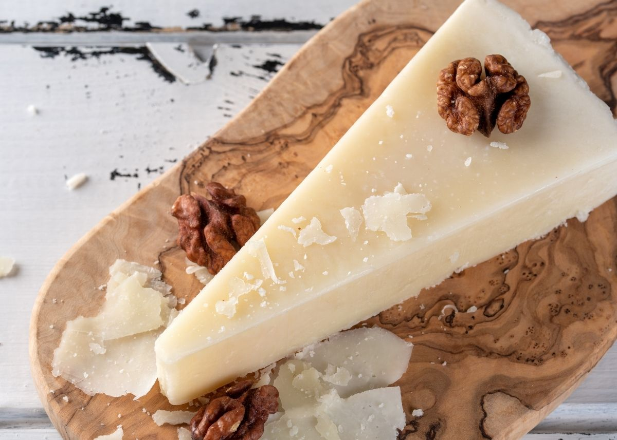 Pecorino Romano cheese wedge on wooden cutting board with shavings and nuts.