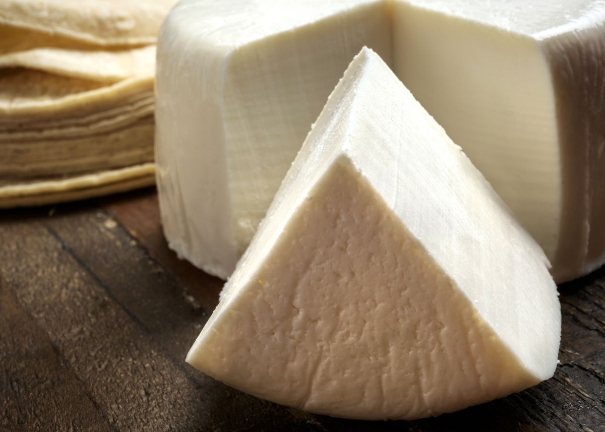 Large wheel of queso fresco cheese with wedge cut out on wooden cutting board.