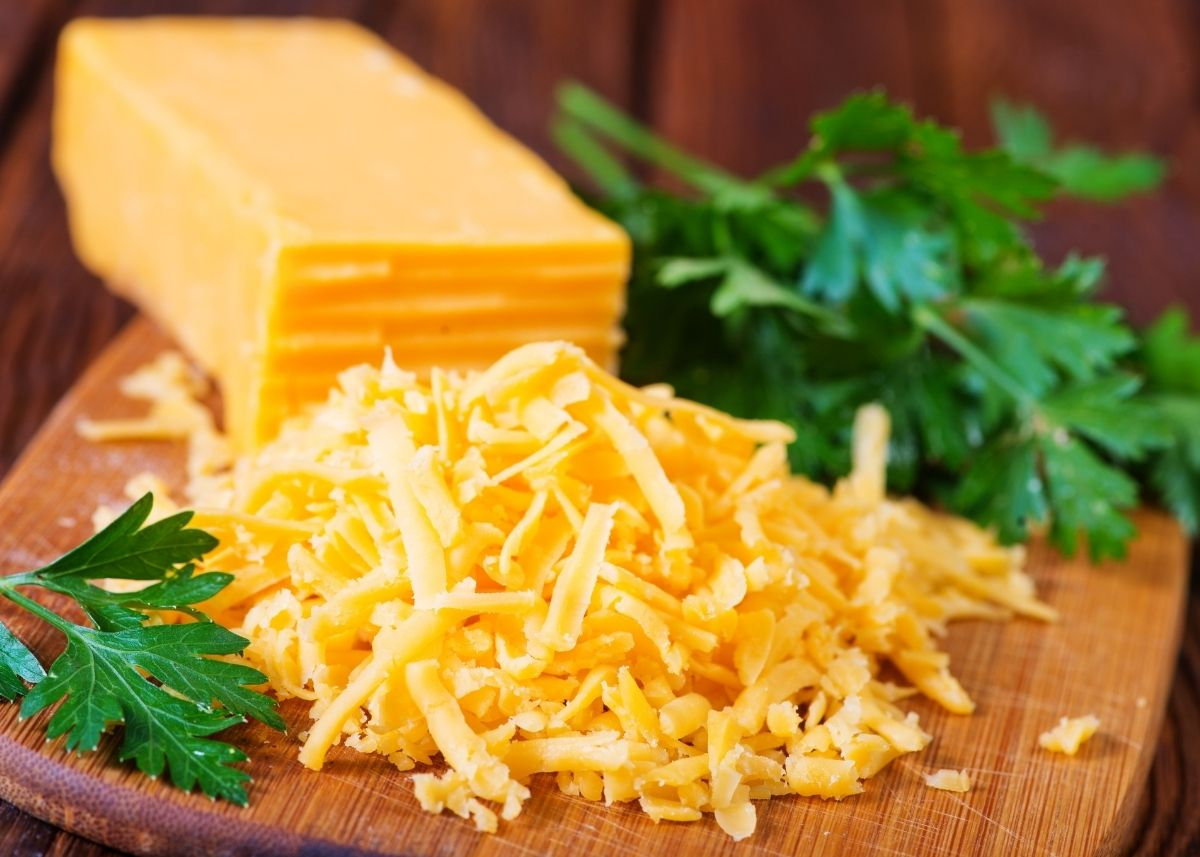 Large block of Red Fox cheddar cheese on wooden cutting board next to shredded cheese.