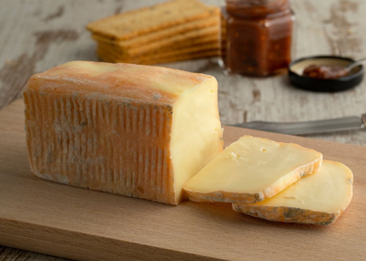 Large block of taleggio cheese next to slices on a wooden cutting board with crackers and jam in background.