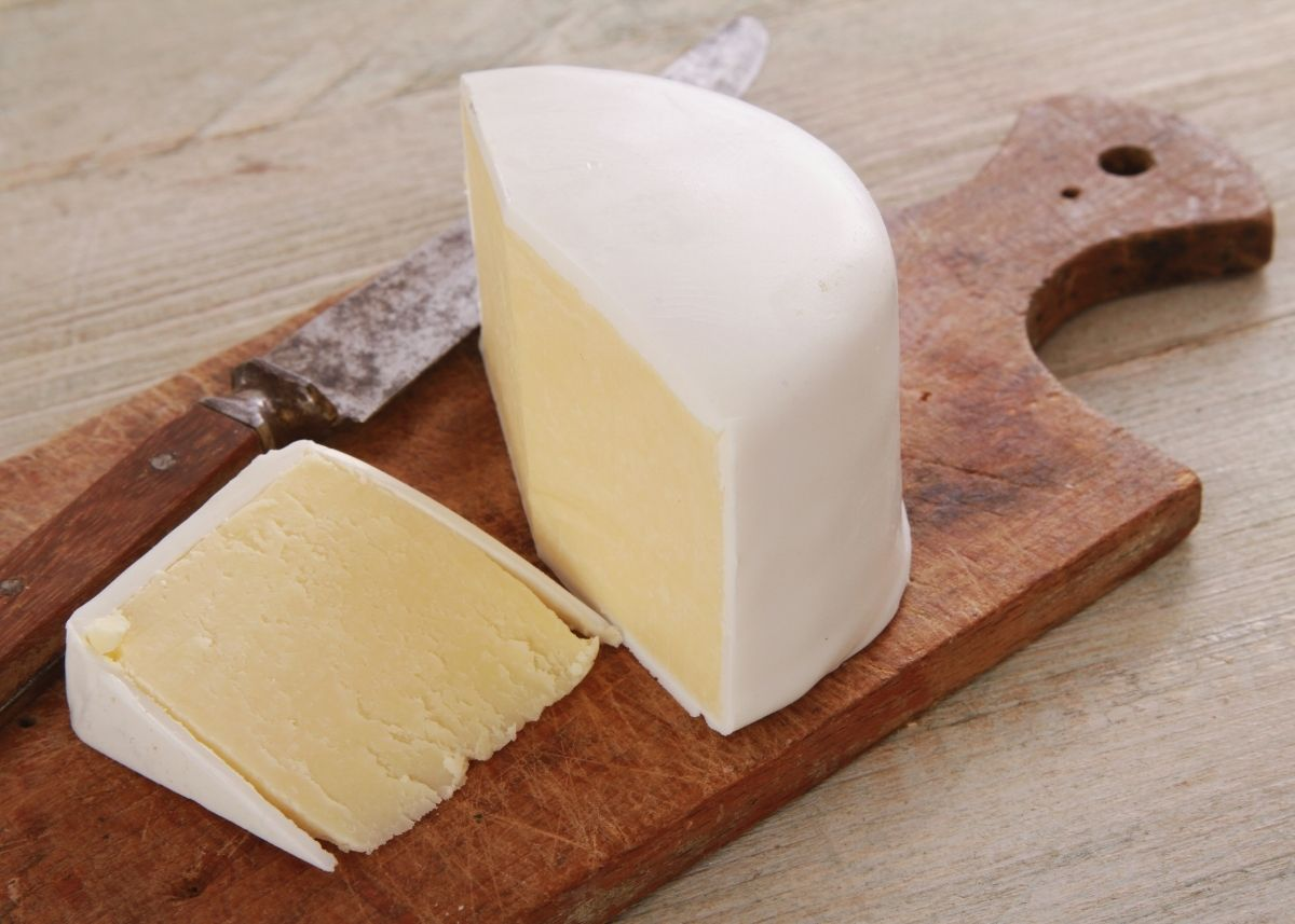 Two large slices of a wensleydale cheese wedge on a wooden cutting board next to knife.