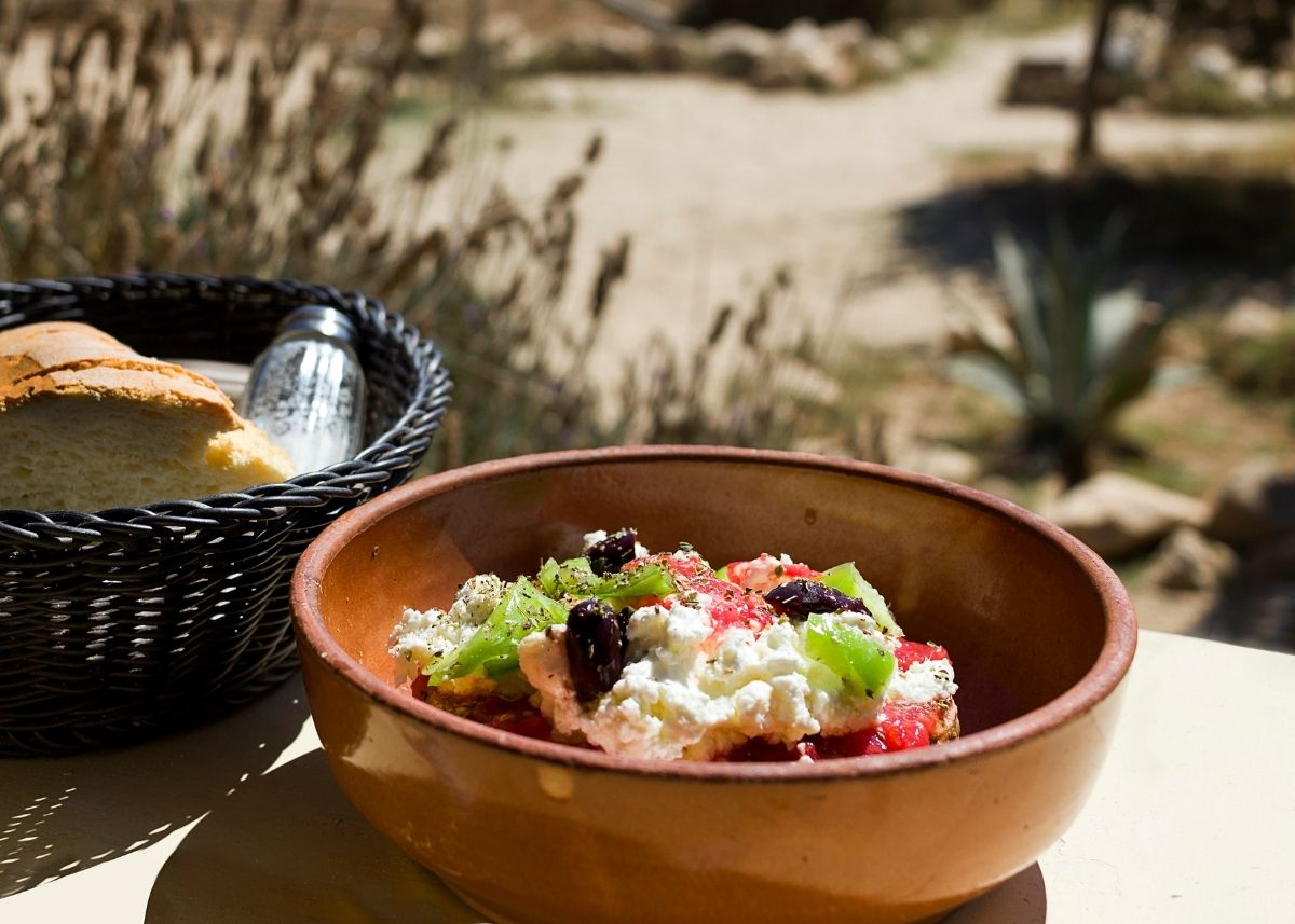 Bowl of mizithra cheese with olives and tomato on top sitting outside on table.