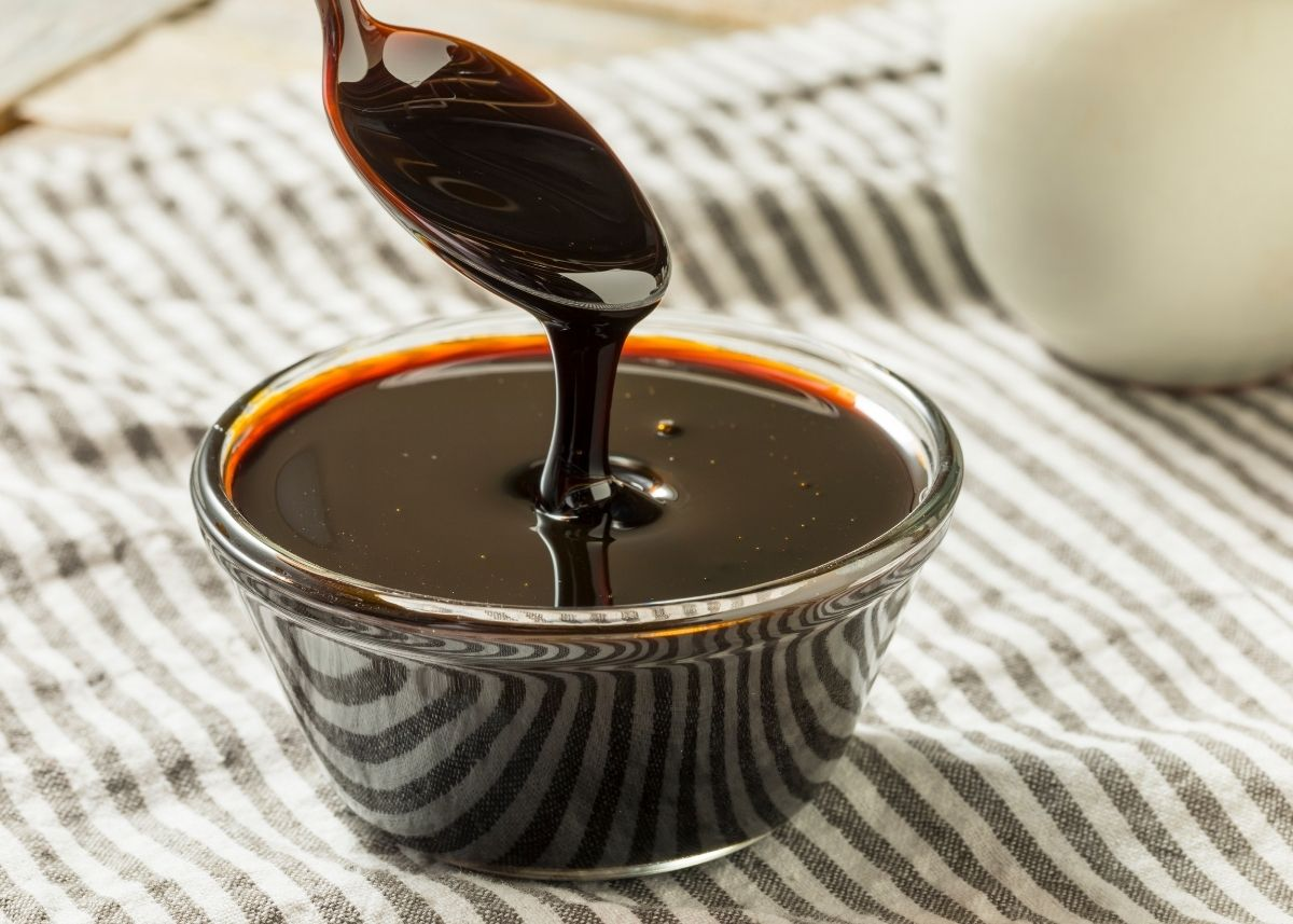 Dark molasses syrup spills from spoon into a clear bowl of molasses on stripe towel.