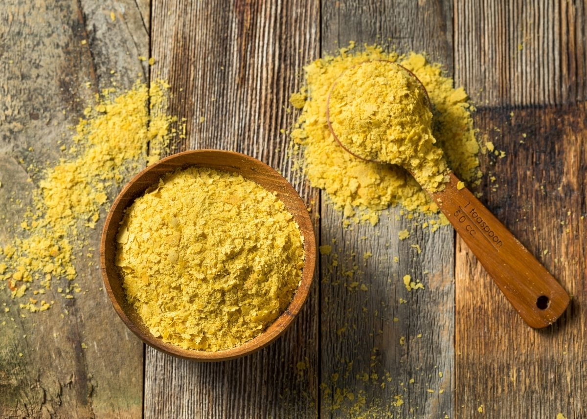 Large bowl of nutritional yeast next to a spoon filled with nutritional yeast.