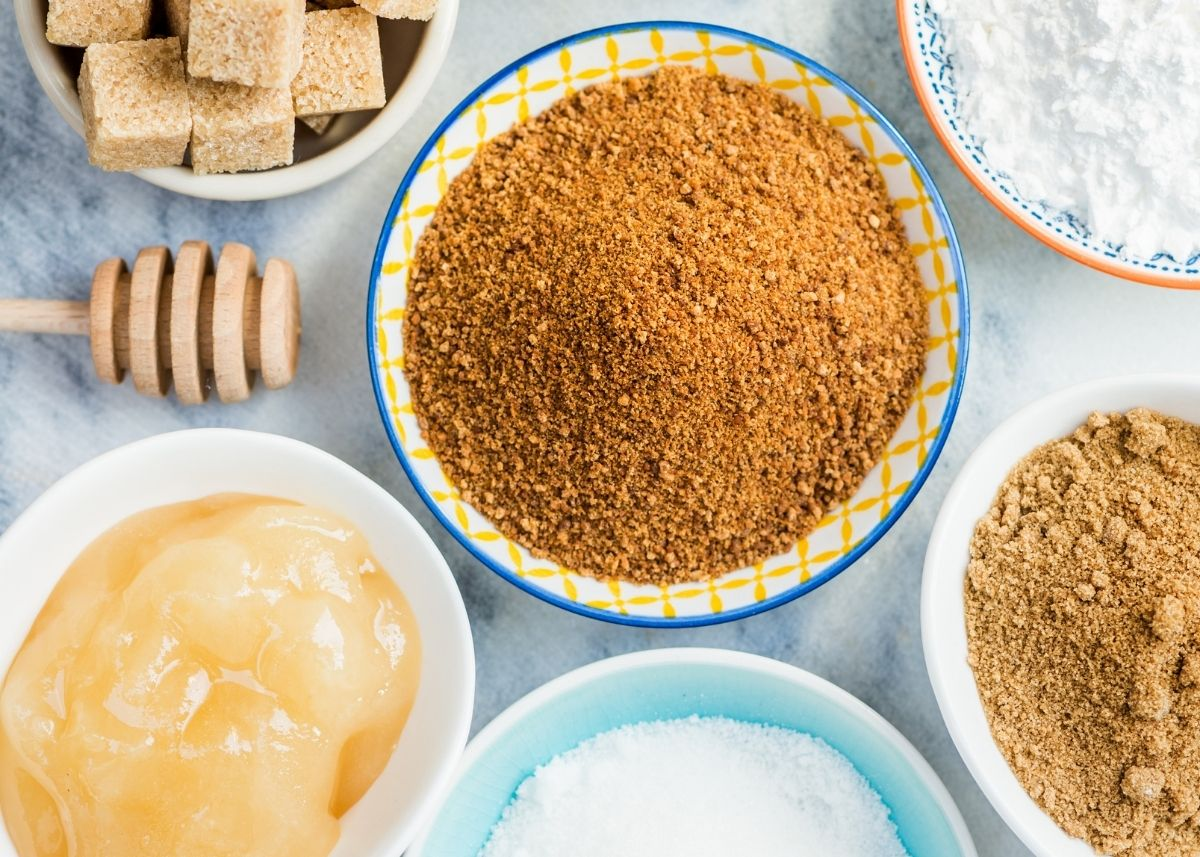 Several bowls of various kinds of sugar and baking ingredients next to a honey dipper.