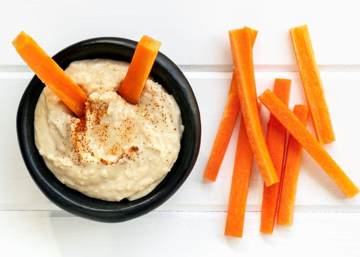 Two carrots stick out of a bowl of hummus next to carrots on a table.