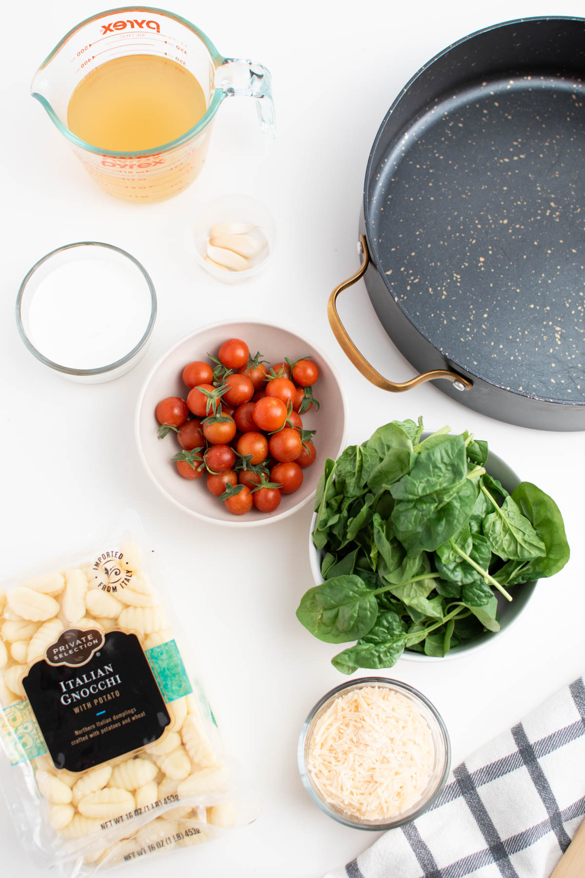 Creamy gnocchi ingredients including tomatoes, spinach, cheese, and cream on white table.