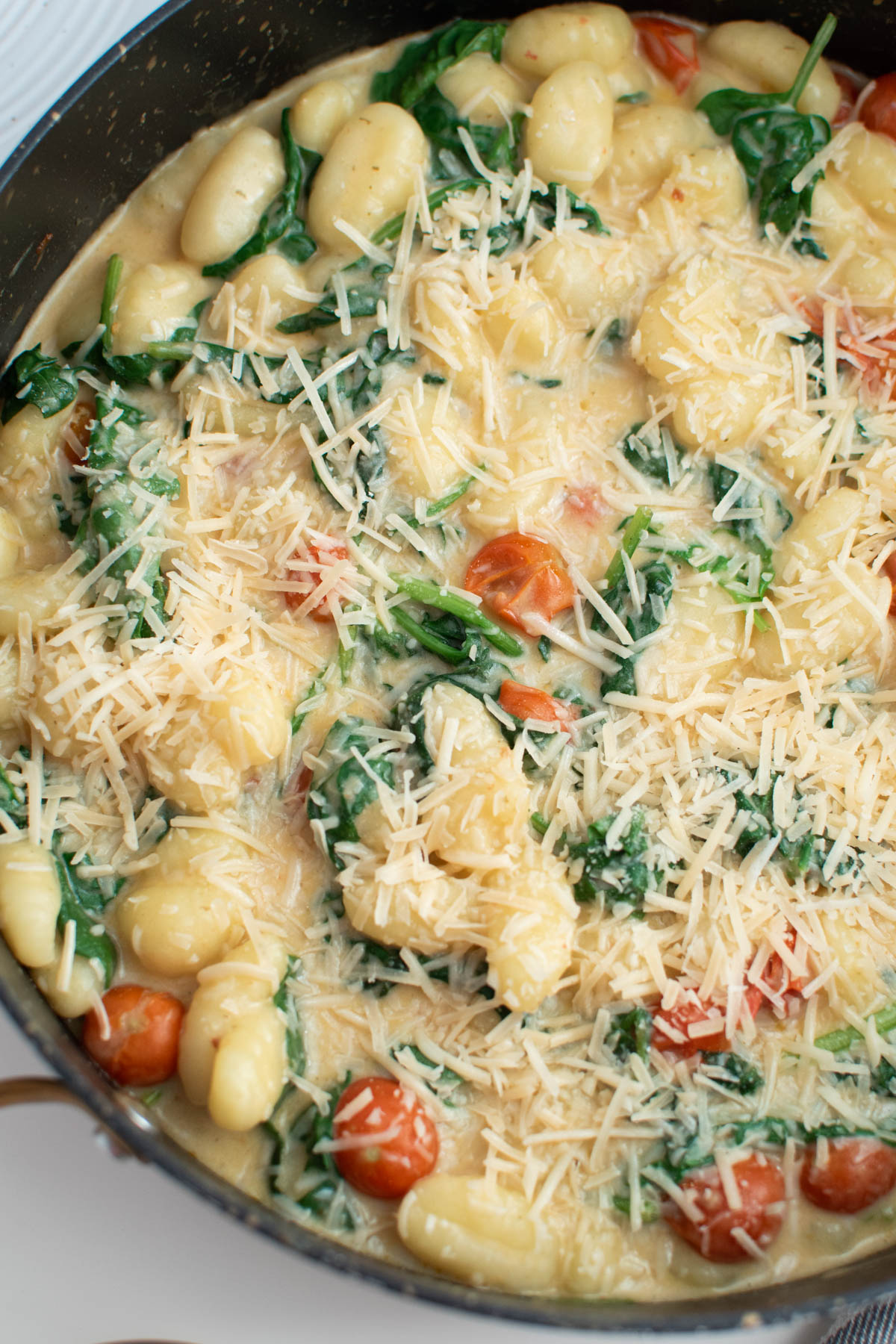 Creamy gnocchi with tomatoes, spinach, and parmesan cheese in large black skillet.