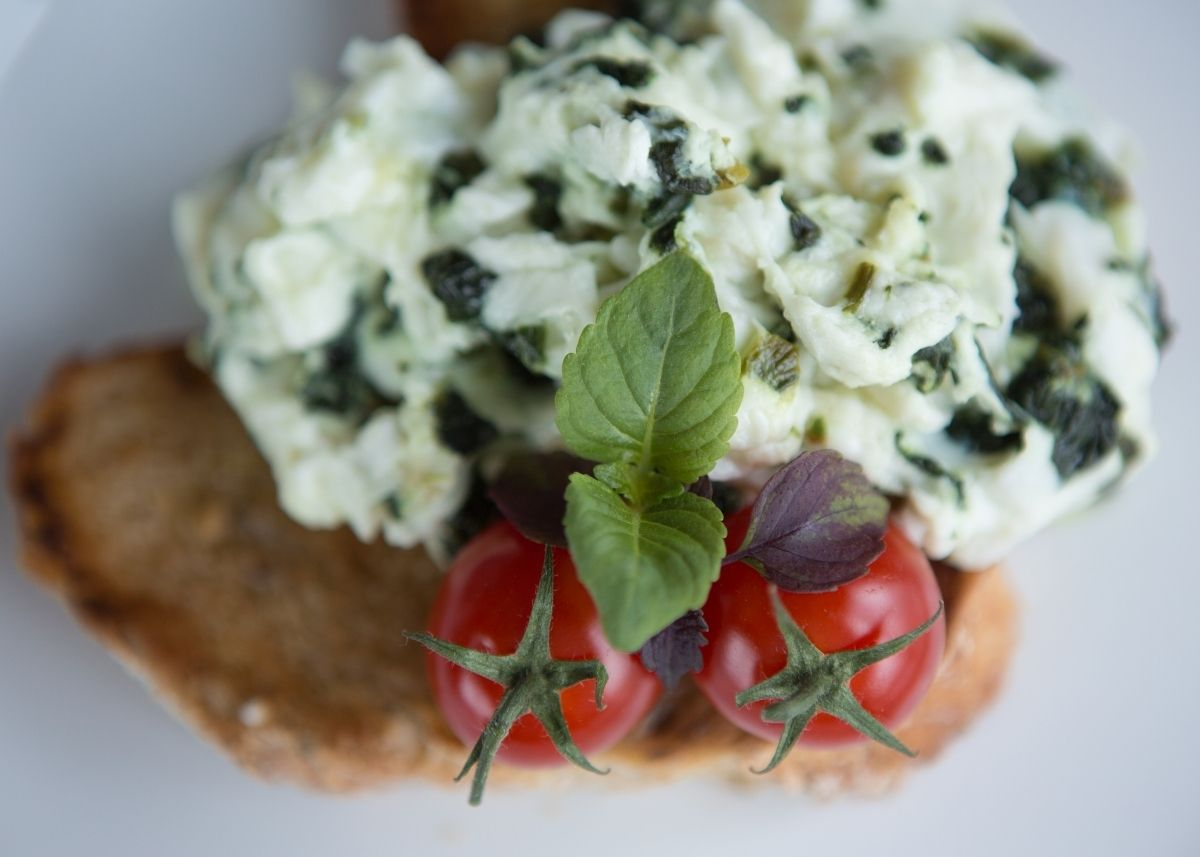 Scrambled egg white with spinach over tomatoes and toast garnished with basil.