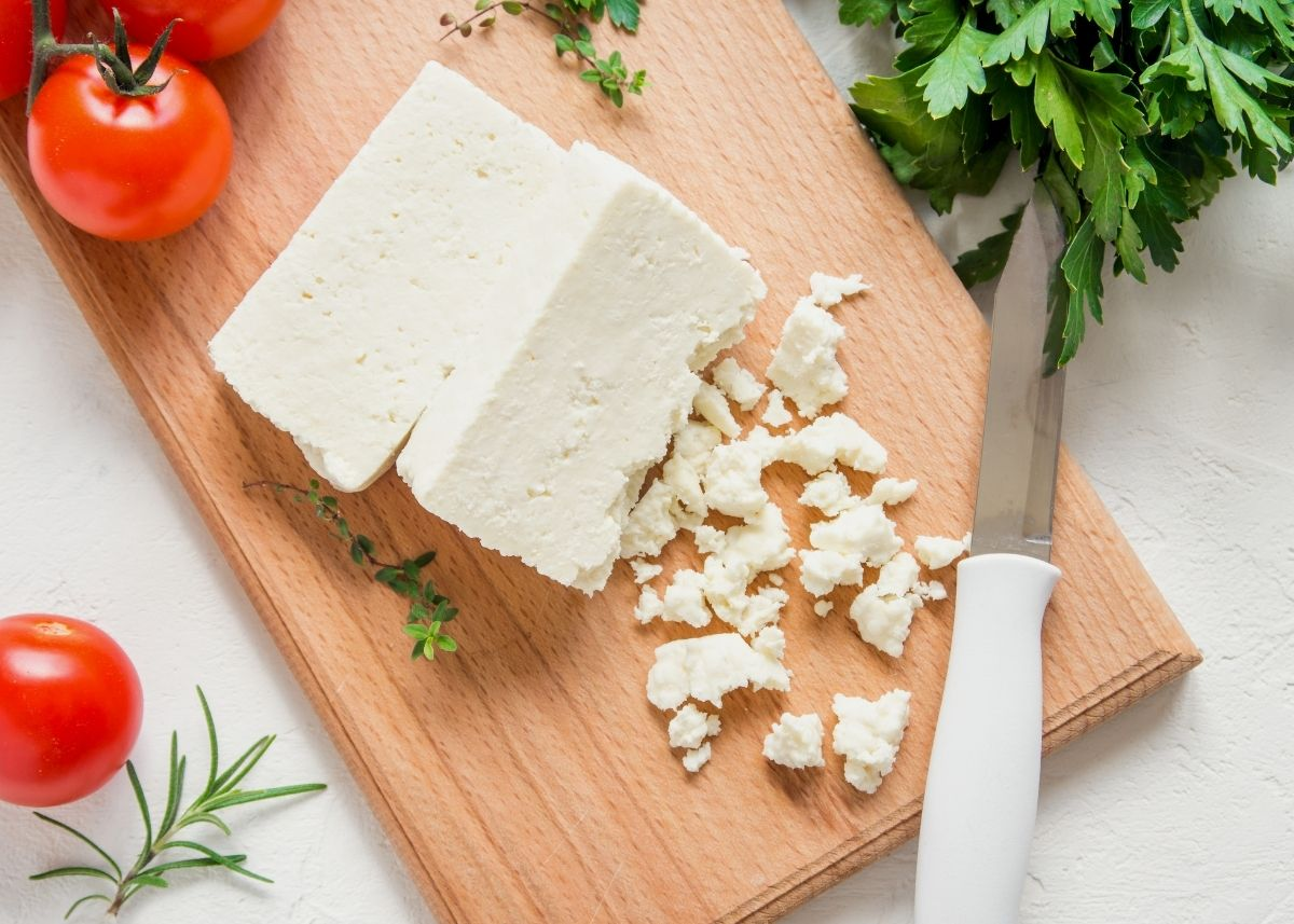 Two blocks of feta cheese on a wooden cutting board next to crumbles surrounded by tomatoes and herbs.