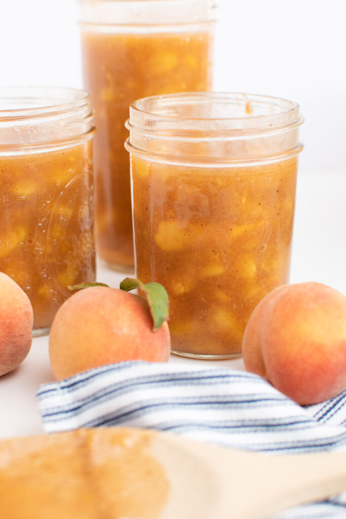 Three jars of freezer peach pie filling surrounded by fresh peaches and striped towel.