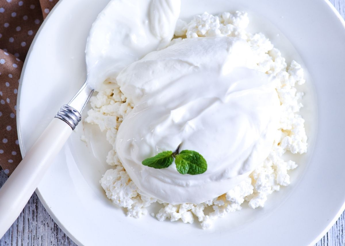 Large mound of fromage blanc over cottage cheese on white plate with green garnish.