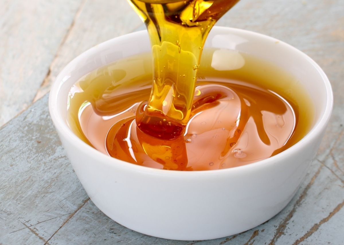 Golden syrup drips from a spoon into a white ramekin over a wooden table.