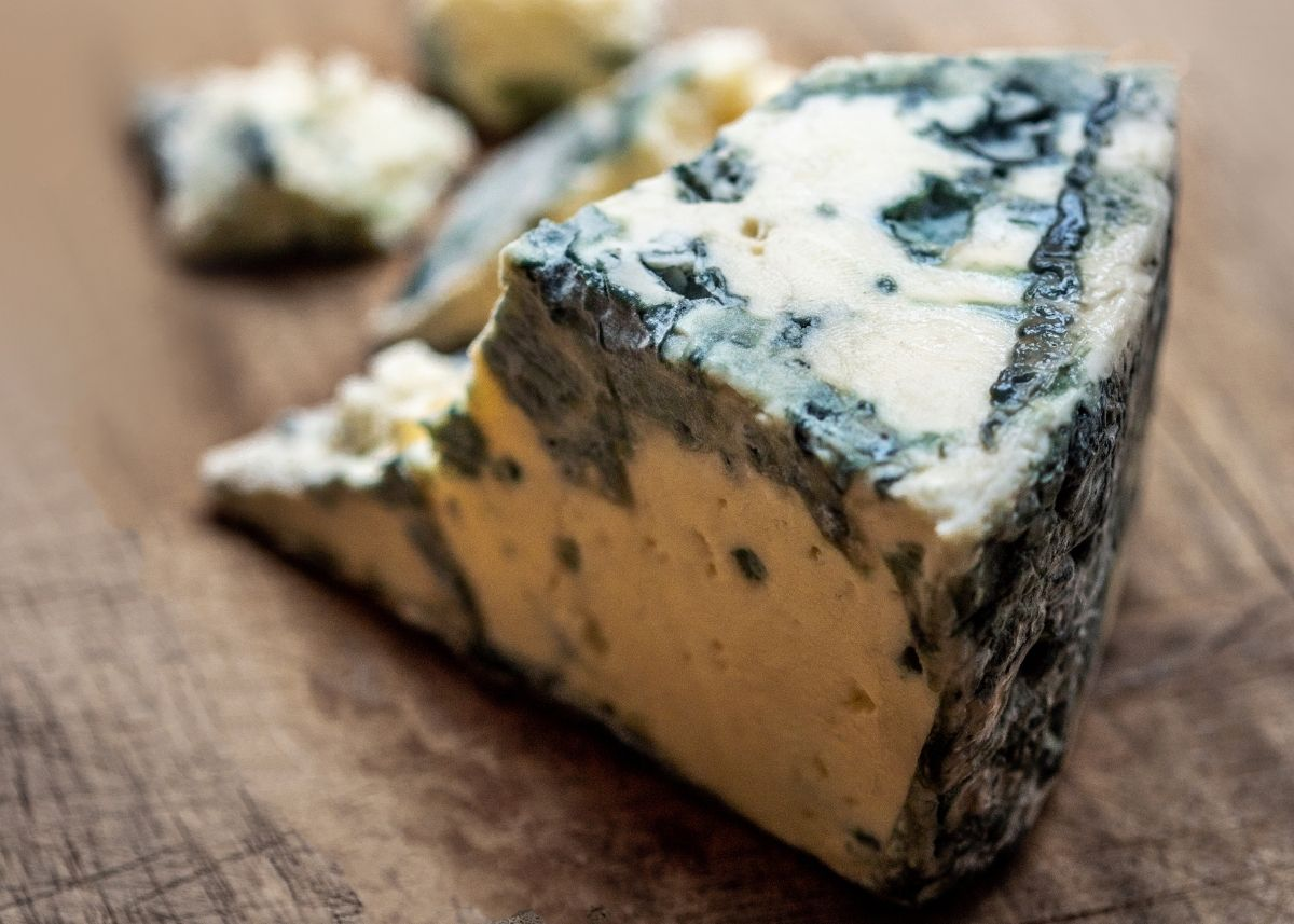 Large wedge of gorgonzola blue cheese with crumbles on a rustic wooden table.