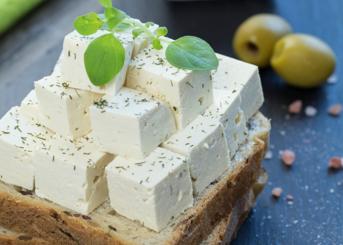 Several cubes of homemade tofu vegan feta piled on a piece of bread.