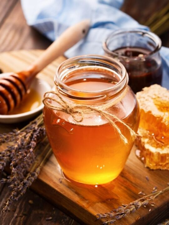 Jar of honey next to chunk of honeycomb and honey dipper on cutting board.