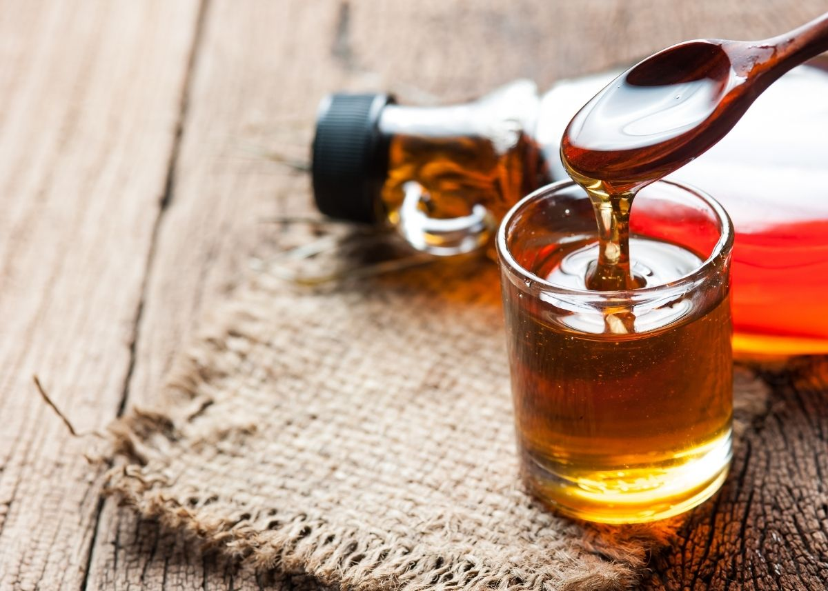 Maple syrup is poured from a spoon into a glass on a burlap cloth.