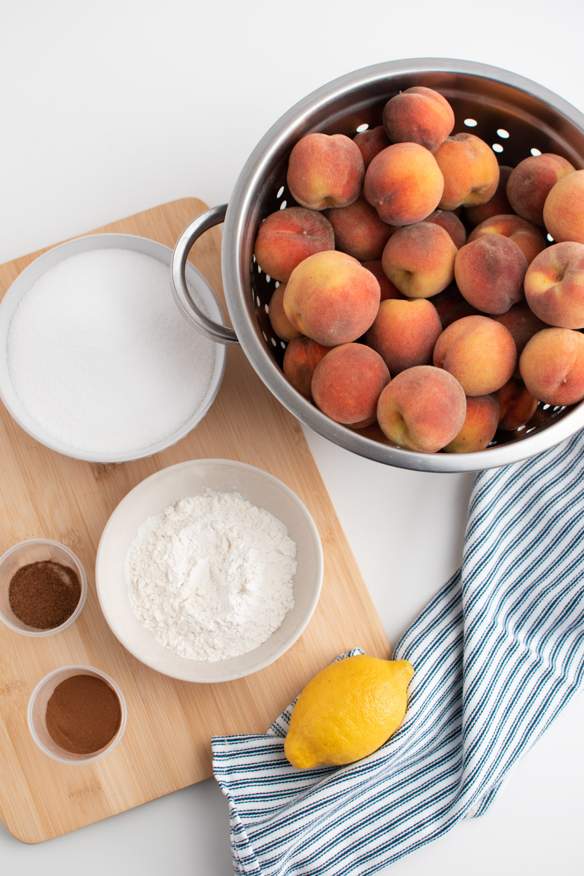 Various peach pie filling ingredients like peaches, sugar, flour, and spices on cutting board and white table.