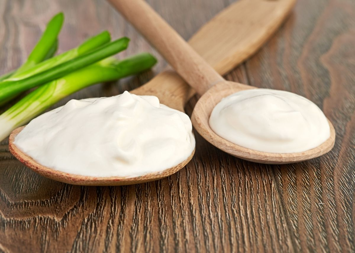Sour cream on two large wooden spoons next to green onion sprigs.