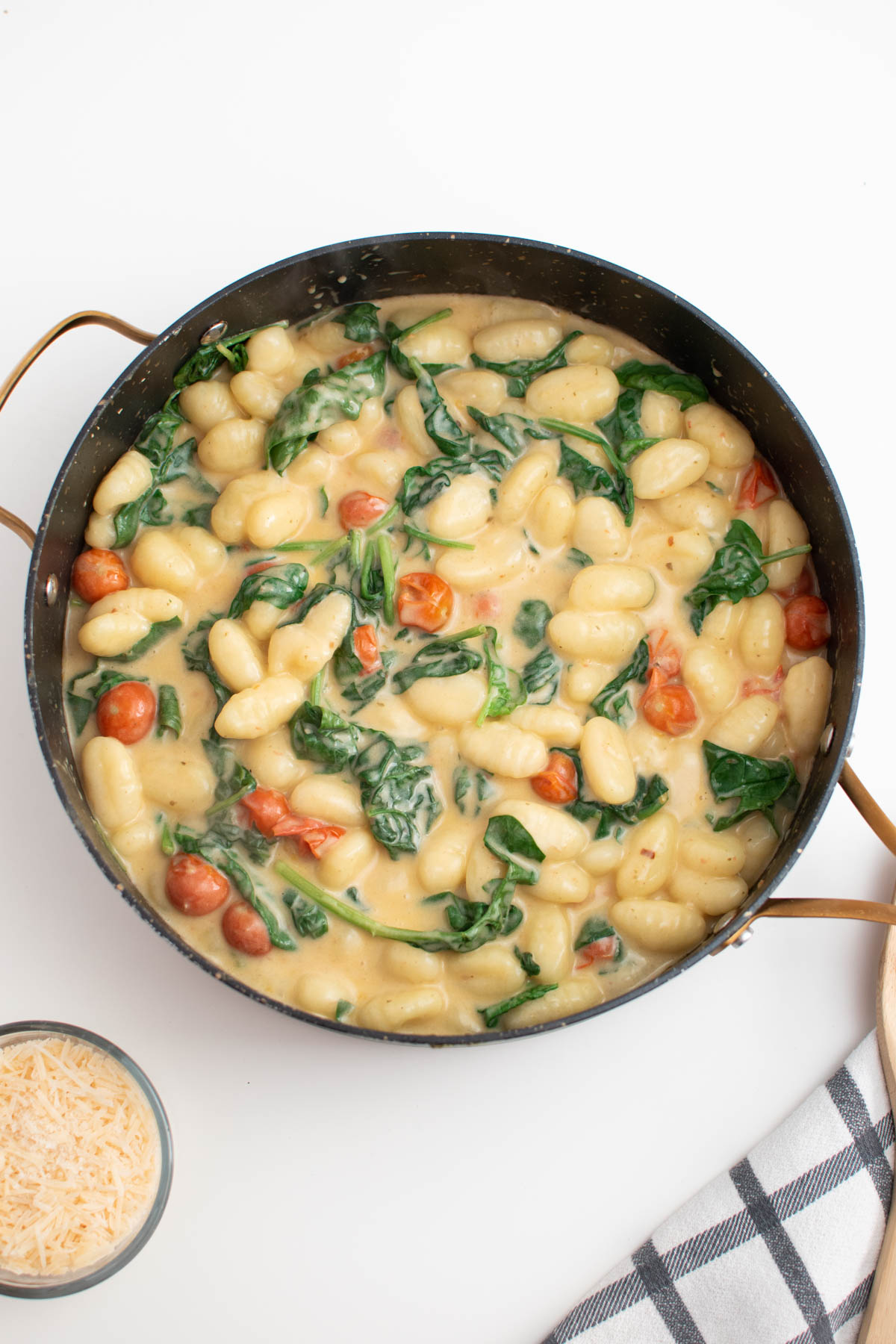 Large black skillet full of gnocchi, tomatoes, and spinach next to bowl of parmesan cheese.