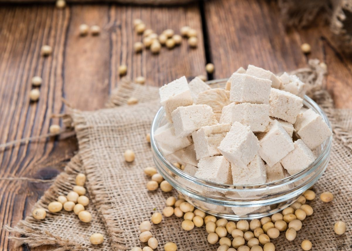 Glass bowl piled high with cubes of tofu surrounded by soybeans.