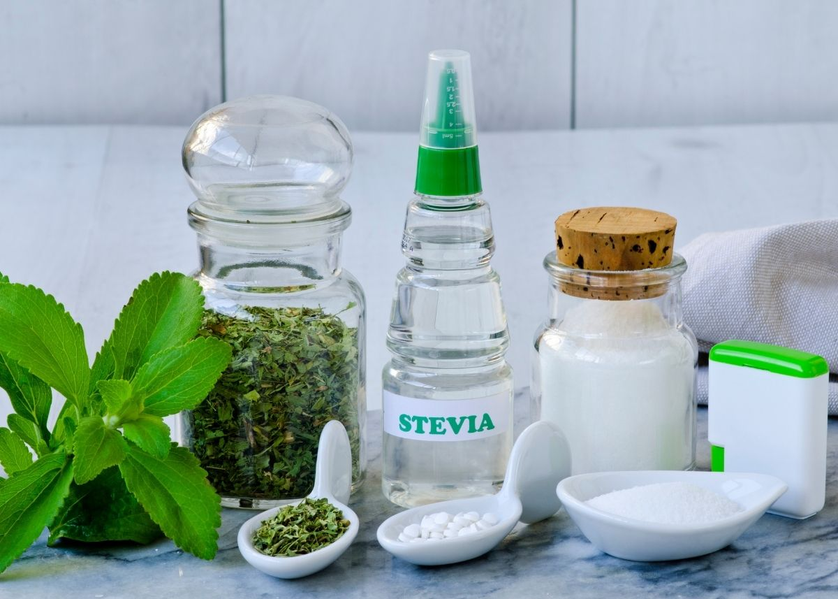 Various forms of stevia in glass containers next to bundle of mint and dried mint flakes.