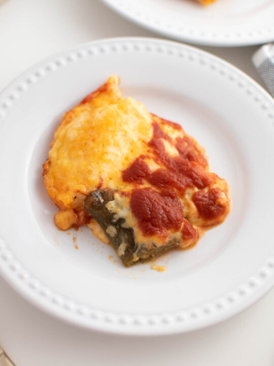 Slice of cheesy chile relleno casserole on white plate sitting on white table.