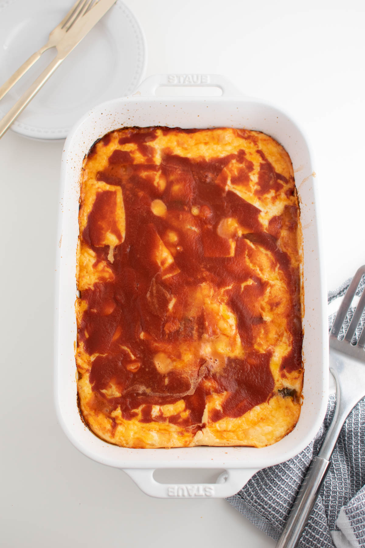 Baking dish of chile relleno casserole on white table surrounded by plates and spatula.