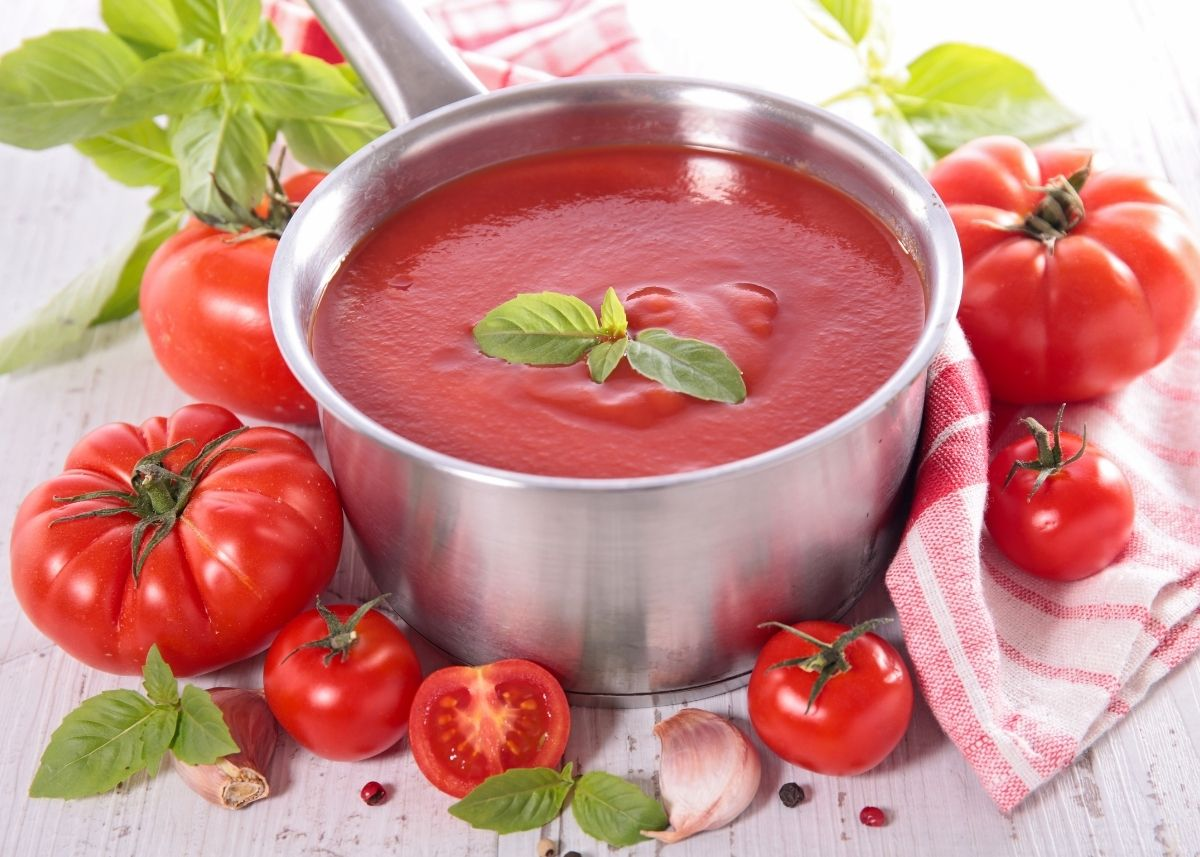 Metal sauce pot filled with homemade tomato sauce surrounded by fresh tomatoes and garnish.