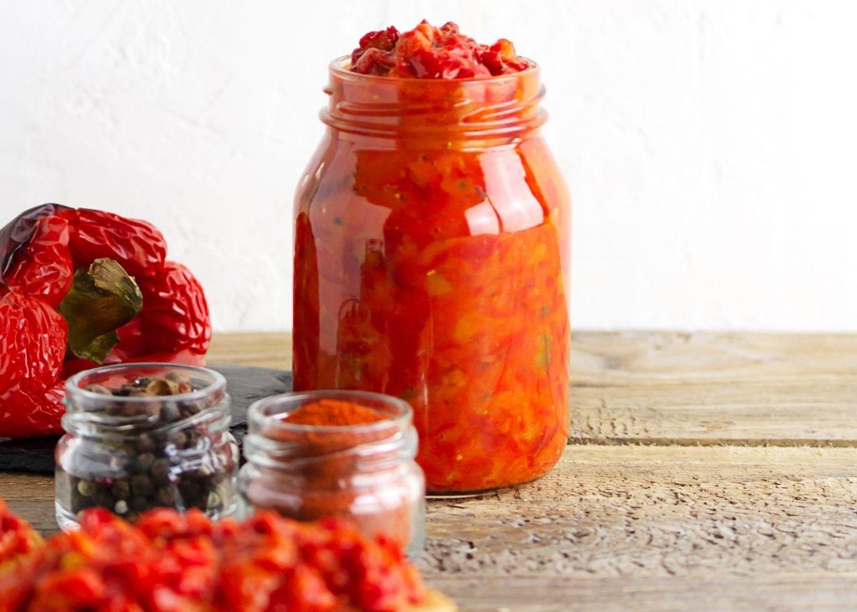 Large jar of avjar next to roasted red bell pepper and seasonings.