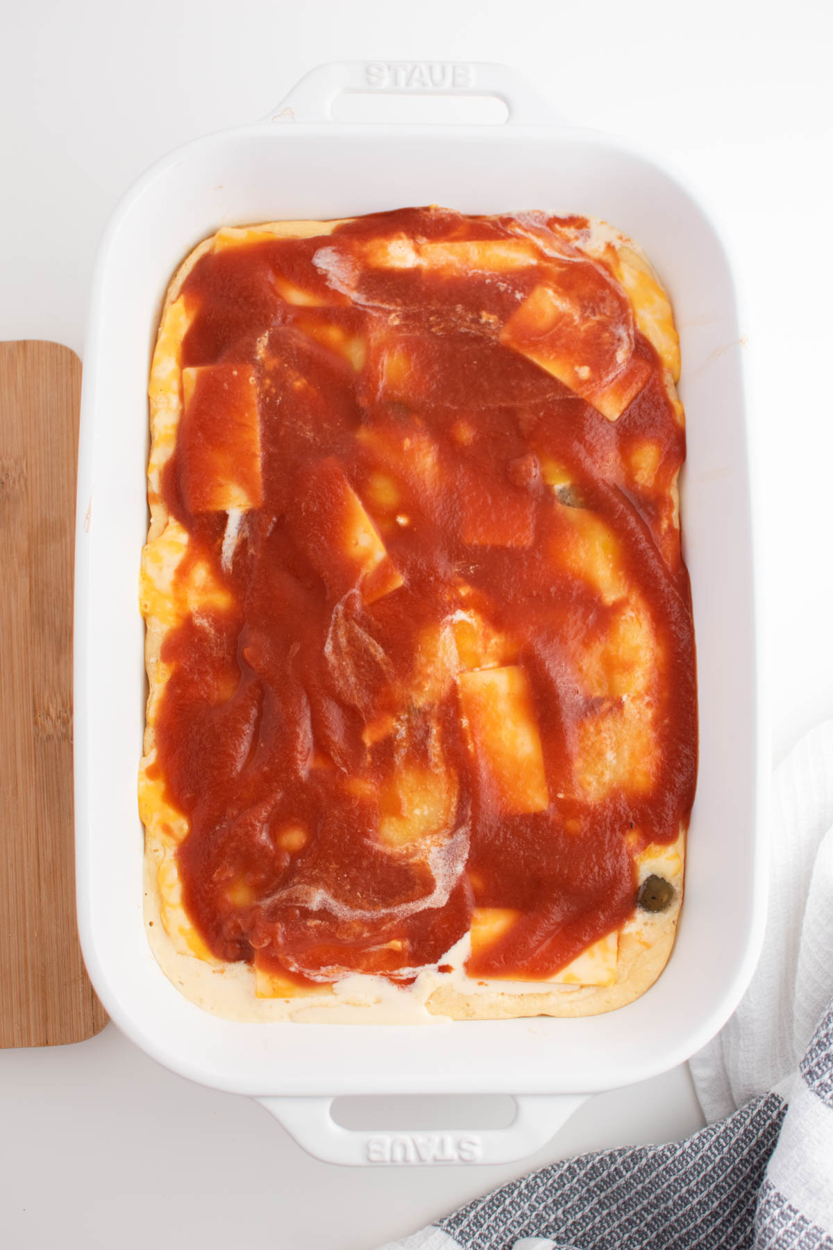 Tomato sauce on half baked chile relleno casserole in white baking dish.