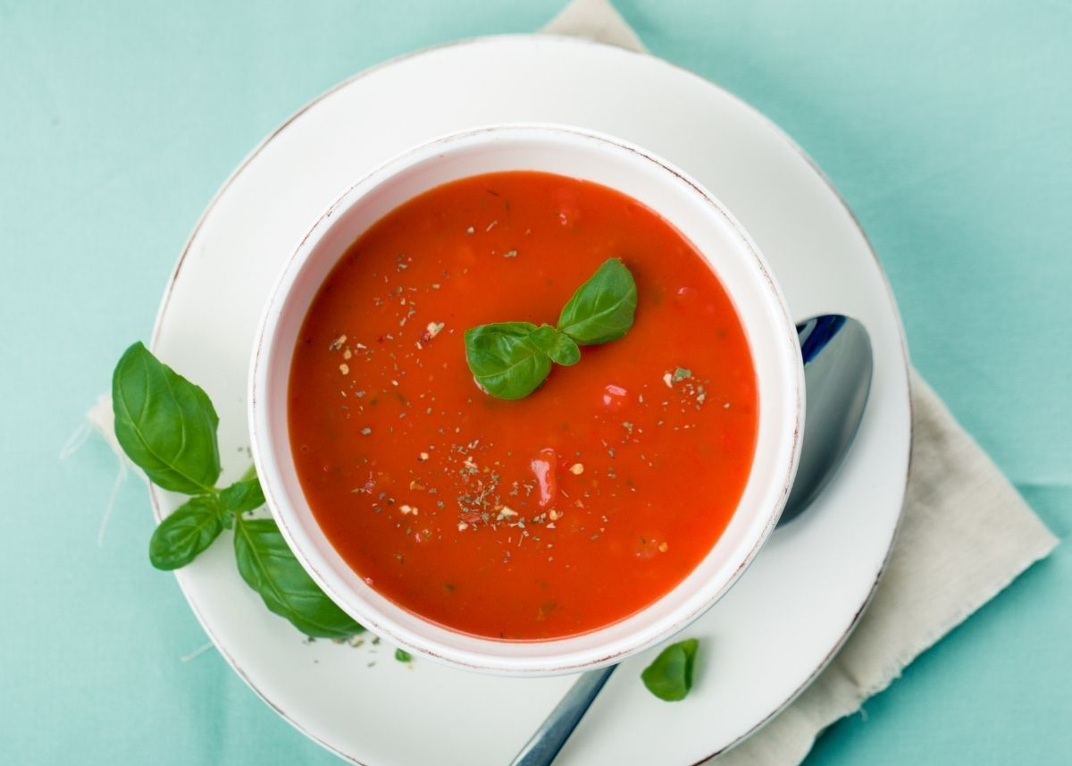 Tomato soup in a white bowl over a white plate with green garnish.