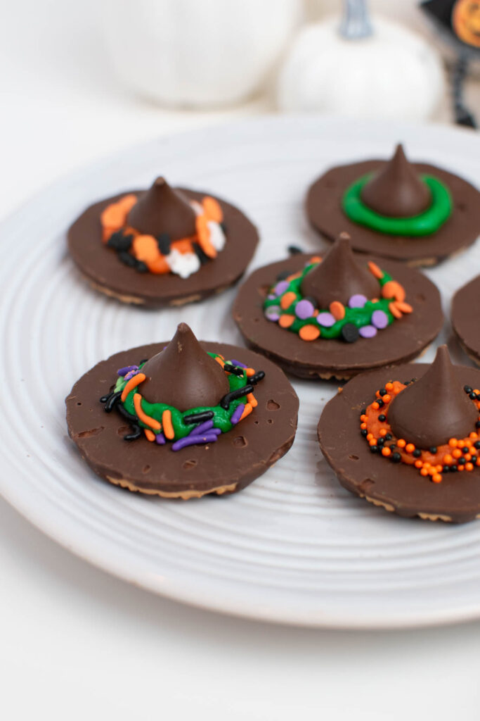 Close up of witch hat cookies with Halloween sprinkle decorations on white plate.
